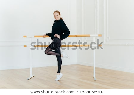 Positive slim young female stands sideways, poses on one leg, dr Stock photo © vkstudio