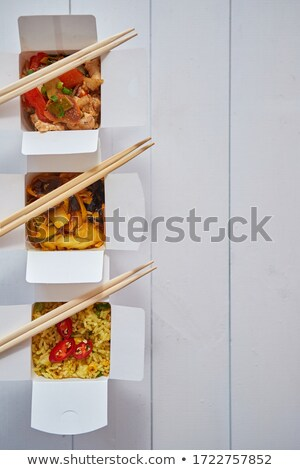 Three take away paper boxes filled with asian food placed in row on white Stock photo © dash