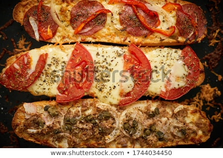 Long baguettes pizza sandwiches with tuna, mushrooms, tomatoes and cheese on a metal baking tray Stock photo © dash