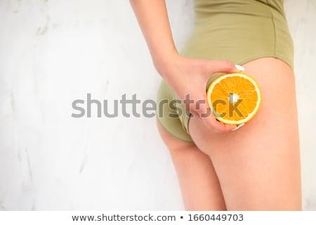 Fiatal lány tart narancs kéz csípők narancsbőr Stock fotó © dashapetrenko