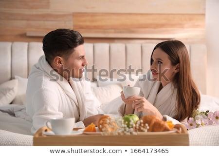 улыбаясь молодым человеком халат завтрак сидят Сток-фото © deandrobot