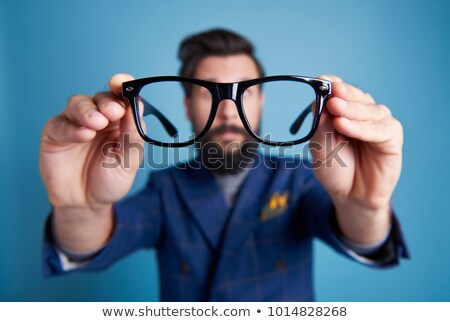 Businessman putting his eyeglasses on to look for an object Stock photo © photography33