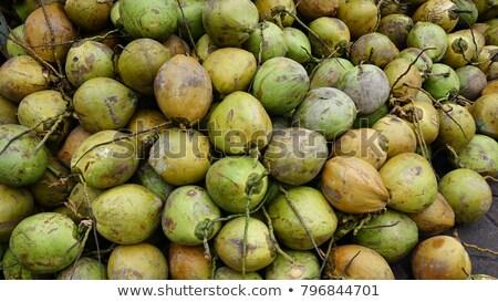 woman holding freshly opened coconut at tropical beach stock photo © kzenon