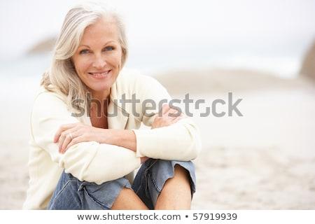 Portrait of smiling woman sitting on shore Stock photo © wavebreak_media