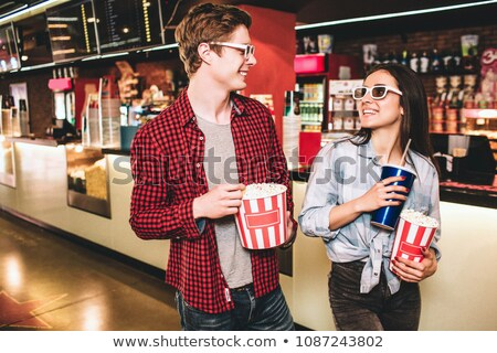 Happy couple having popcorn while watching movie in theatre Stock photo © wavebreak_media