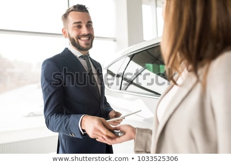 handsome young car salesman standing at the dealership stock photo © deandrobot