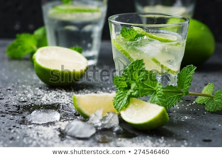 Stock photo: Refreshing mint cocktail mojito with rum and lime, cold drink or beverage with ice on black backgrou