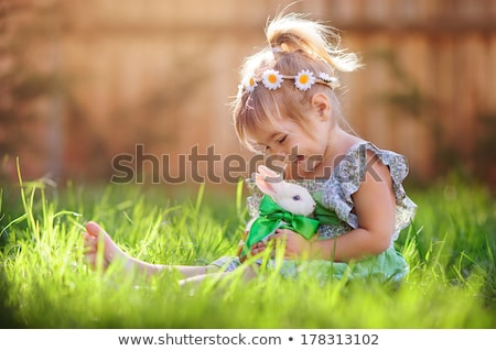 girl playing with rabbit in garden stock photo © is2