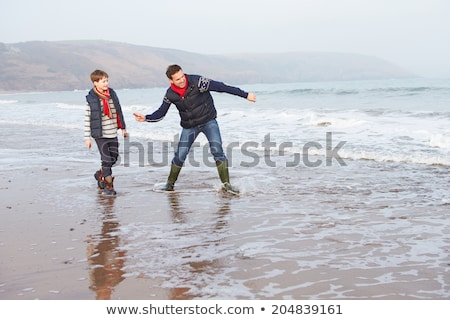 Boy skimming stones out to sea Stock photo © IS2