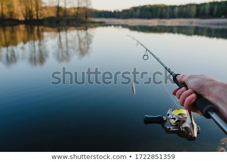 Fisherman with Catch on River and Sunset Backdrop Stock photo © robuart