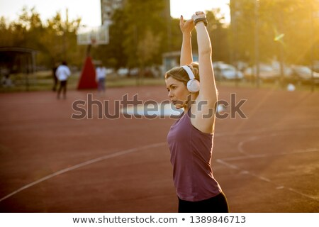 slender fit blonde woman doing stretching before workout stock photo © boggy