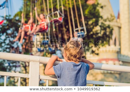 The boy wants to ride on the merry-go-round Stock photo © galitskaya