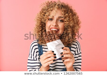Photo of pleased curly woman 20s eating chocolate bar while stan Stock photo © deandrobot