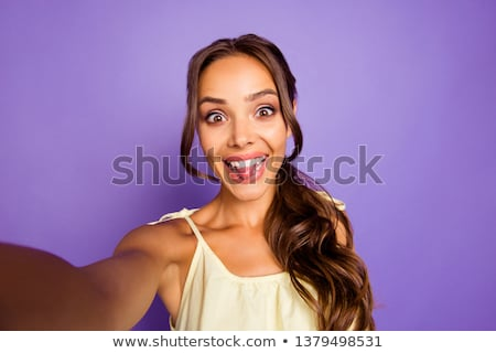 Pretty brunette girl with long wavy hair showing stick out and taking self portrait on her smart pho Stock photo © studiolucky