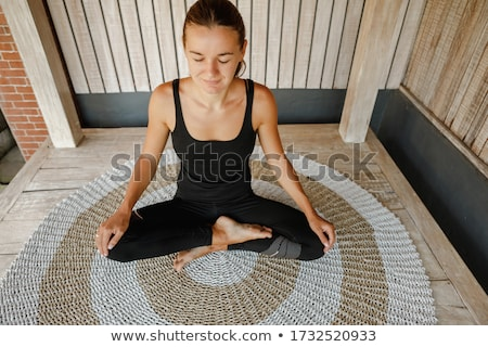 Young woman is practicing yoga in the morning on her balcony with a panoramic view of the city and s Stockfoto © galitskaya