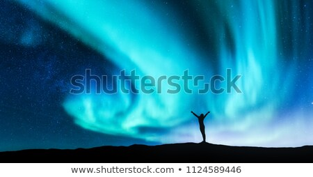 aurora borealis and silhouette of a woman with raised up arms stock photo © denbelitsky