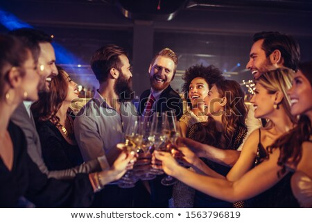 Stock photo: Group of friends enjoying evening drinks In bar