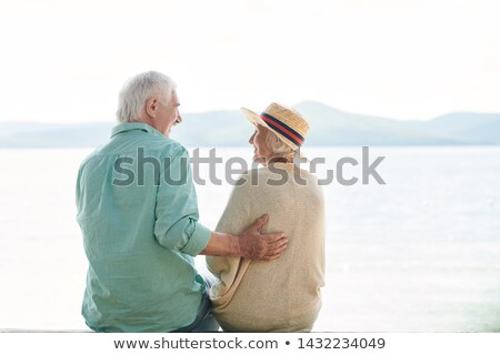 Rear view of casual senior couple chatting by waterside Stock photo © pressmaster