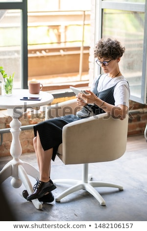 Restful young woman in casualwear scrolling in digital tablet Stock photo © pressmaster