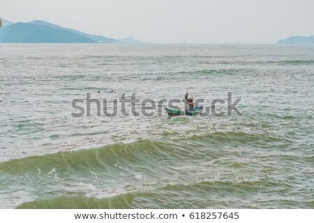 Vietnamese fisherman swims in a boat over the raging sea Stock photo © galitskaya