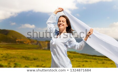 happy woman with shawl waving in wind over big sur Stock photo © dolgachov
