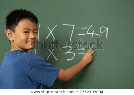 Front view of an Asian schoolboy doing math on greenboard in a classroom at elementary school Stock photo © wavebreak_media