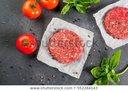 Fresh raw minced pepper beef burger on stone chopping board with buns onion and tomatoes on black ba Stock photo © DenisMArt