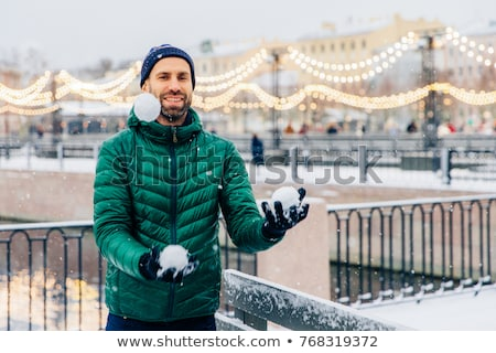 Playful smiling male juggles with snowballs throws them in air,  Stock photo © vkstudio