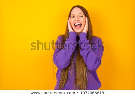 Photo of cute young woman with long hair, pleasant appearance, shows her slim belly, wears white swe Stock photo © vkstudio