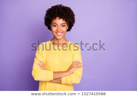 Beautiful young african woman wearing sweater standing over blurred background, looking at camera Stock photo © deandrobot