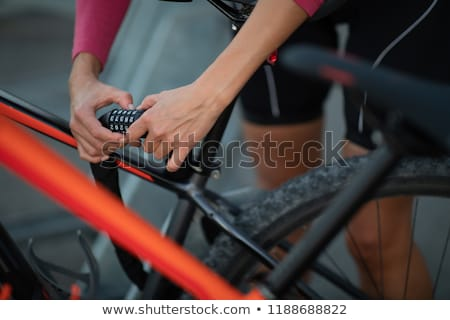 Young woman locking her mountain bike with a numeric lock Stock photo © lightpoet