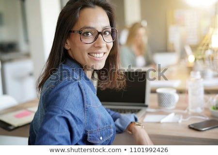 Portrait of young business woman sitting with a laptop on comfor Stock photo © HASLOO