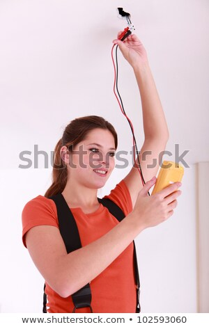 Woman using a voltmeter on ceiling electrics Stock photo © photography33