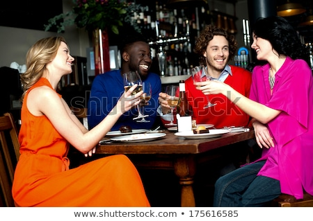 Friends raising their glasses in a toast at a restaurant Stock photo © photography33