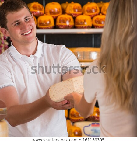Male salesman in cheese store with a female customer Stock photo © HASLOO