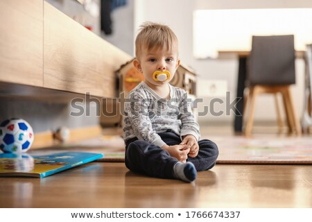 portrait of toddler with pacifier sitting in cot Stock photo © phbcz