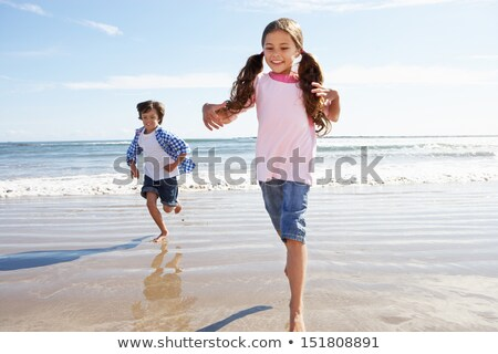 Children Running Away From Breaking Waves On Beach Stock photo © monkey_business