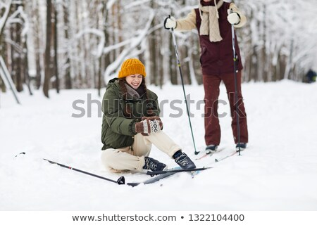 Two young women sitting in snow at a ski resort Stock photo © dash