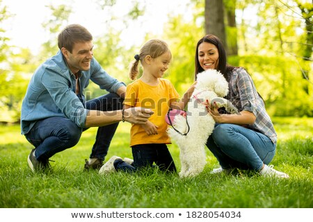 couple of young women playing with a small dog Stock photo © Giulio_Fornasar