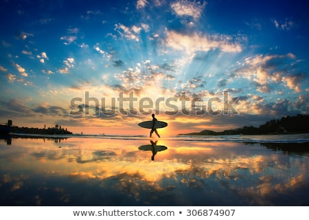 Man walking with surf board across the sea shore Stock photo © deandrobot