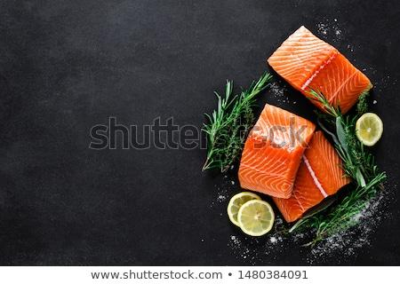 Salmon fish steak with lemon and thyme on black background Stock photo © yelenayemchuk