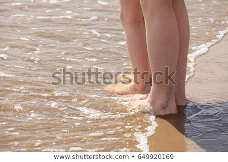 closeup shot of the feet of mother and her child in water beach stock photo © nobilior