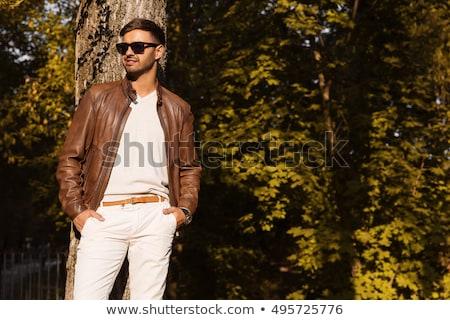 Elegante moço jaqueta de couro olhando câmera sessão Foto stock © 2Design