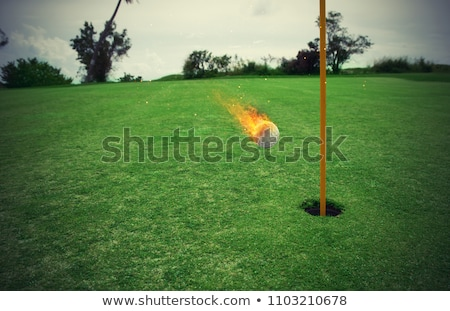 fiery golf ball near the hole in a grass field stock photo © alphaspirit