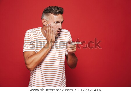 portrait of caucasian adult man grabbing his face and pointing f stock photo © deandrobot