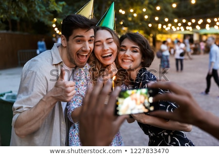 group of cheerful multhiethnic friends celebrating stock photo © deandrobot