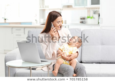Stock photo: working mother with baby calling on smartphone