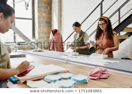 Young male designer of fashion looking at textile samples in catalogue Stock photo © pressmaster