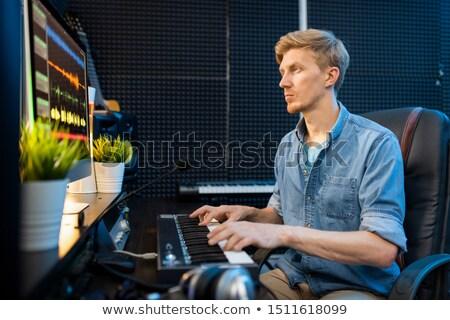 Fiatalember néz képernyő kisajtolás kulcsok zongora Stock fotó © pressmaster
