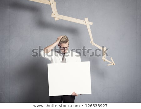 frustrated businessman holding panel in front of graph pointing stock photo © lichtmeister